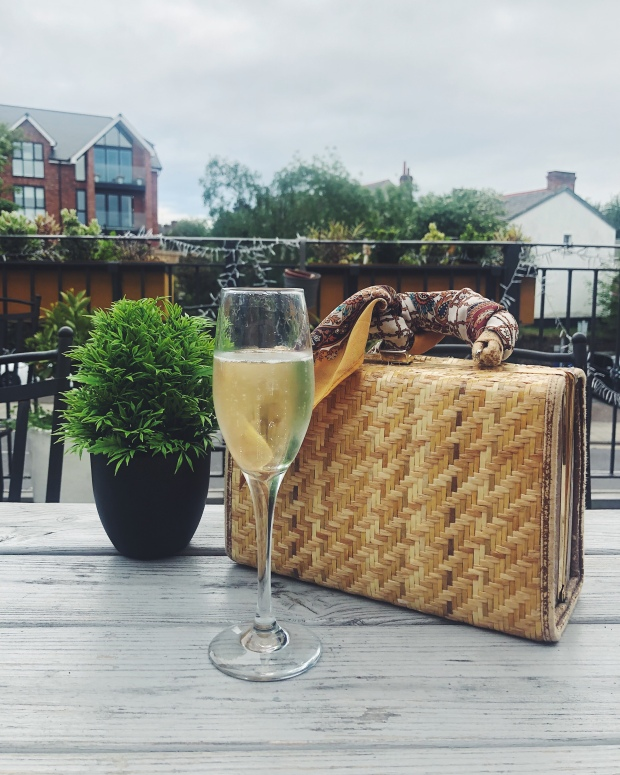 Glass of Prosecco and handbag