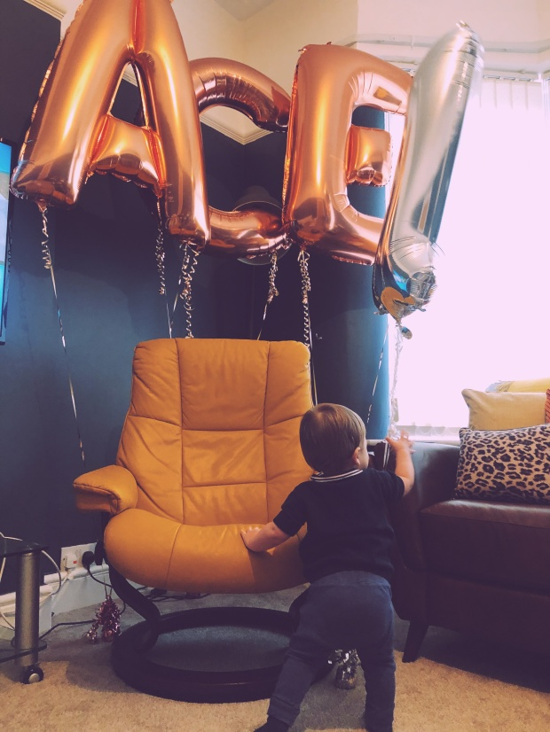 Baby boy with birthday balloons