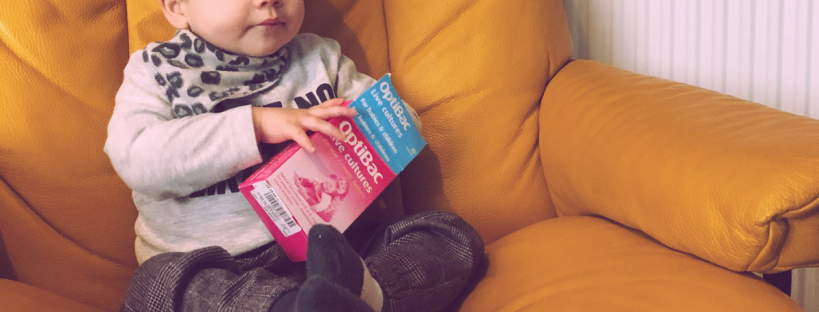 baby holding a box of probiotics