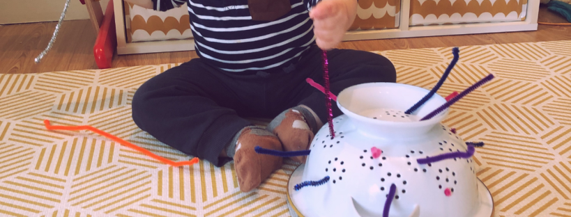 baby boy playing with pipecleaners in a collindar