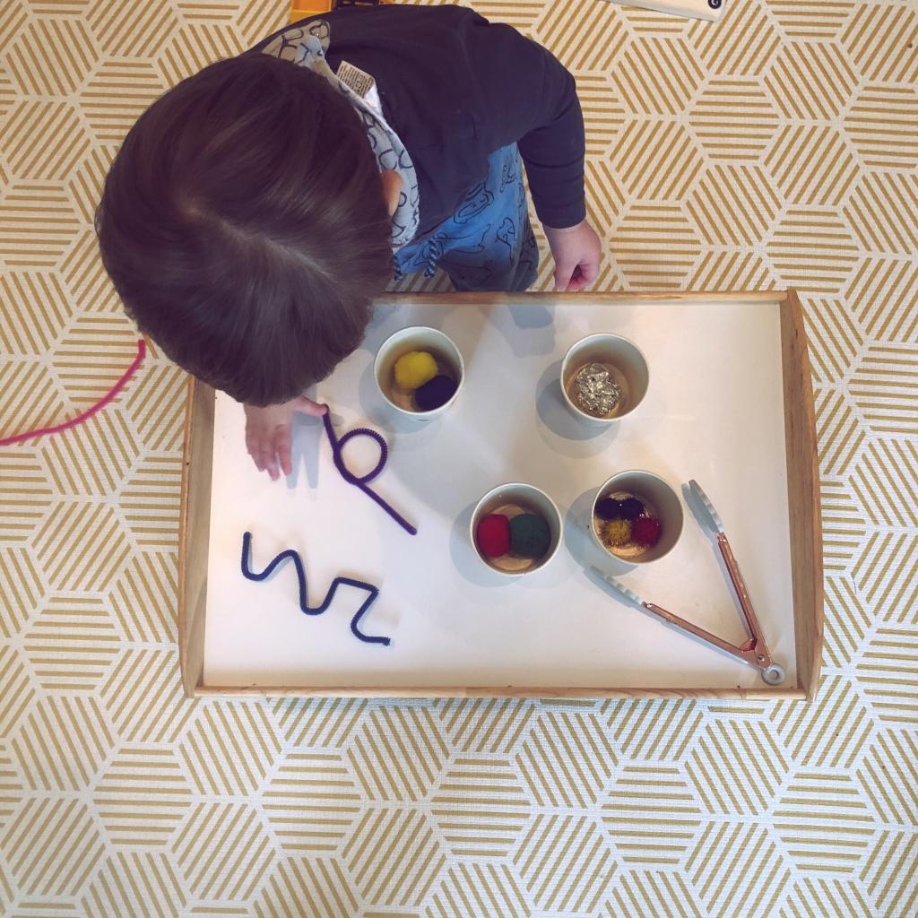 Baby boy playing with Pom Poms