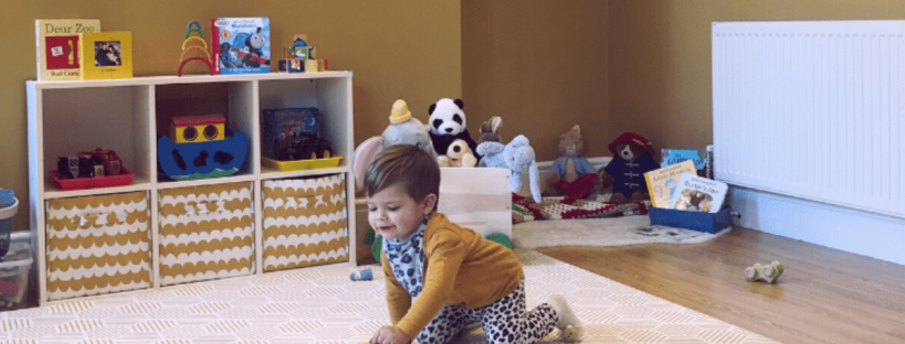 little boy playing in a yellow playroom