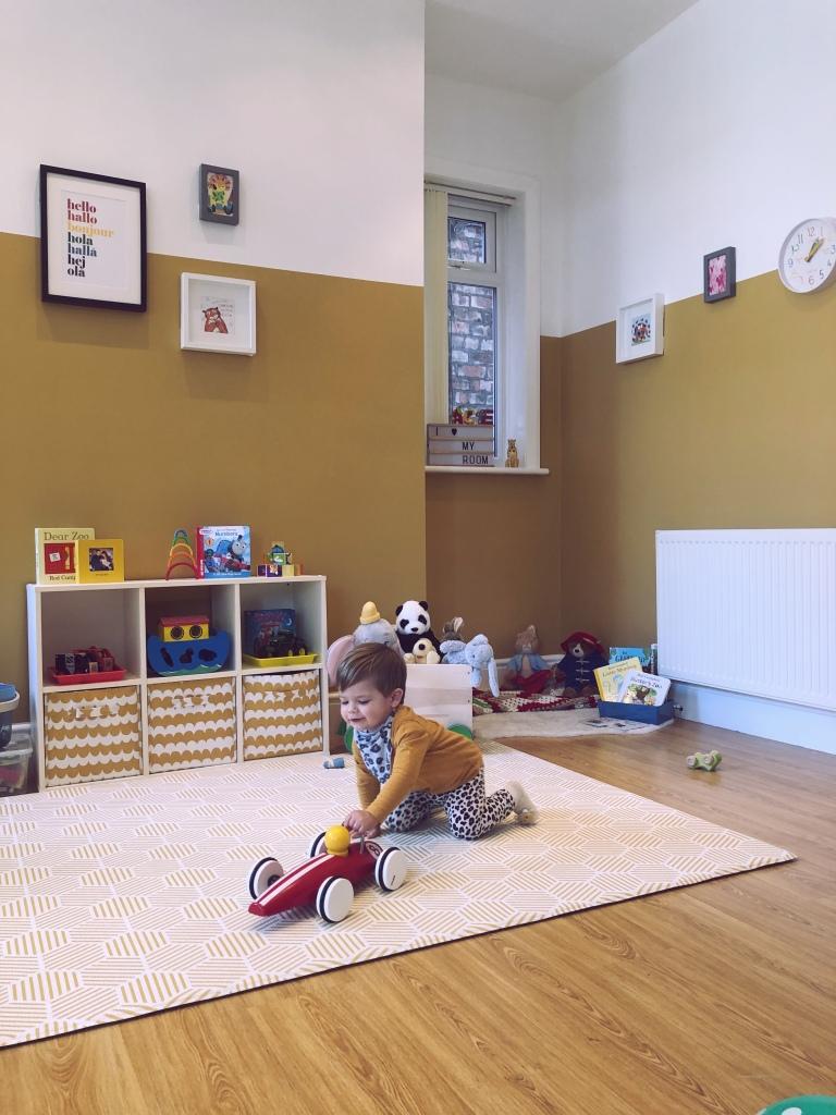 Baby boy in yellow playroom