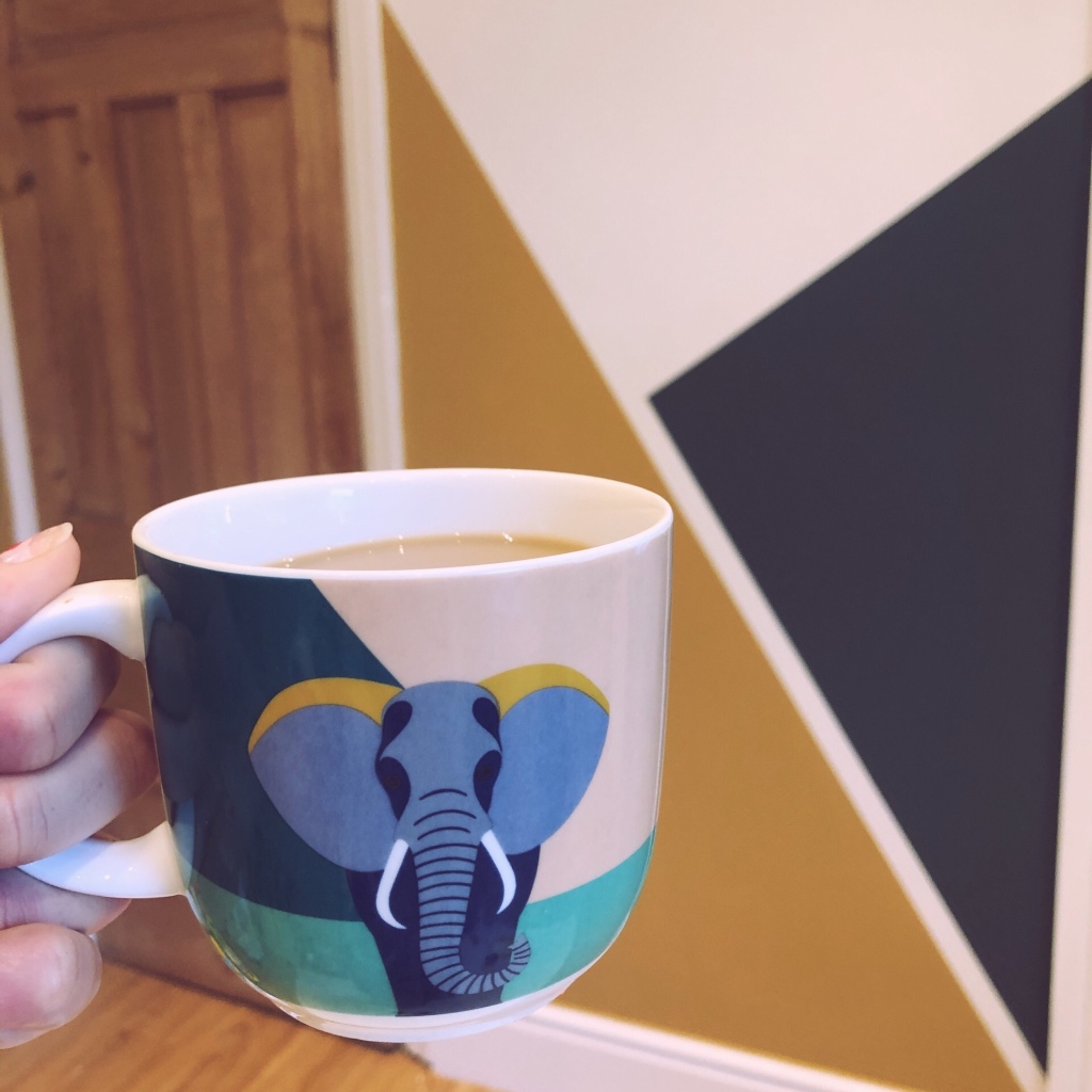 Mug in front of yellow and blue wall