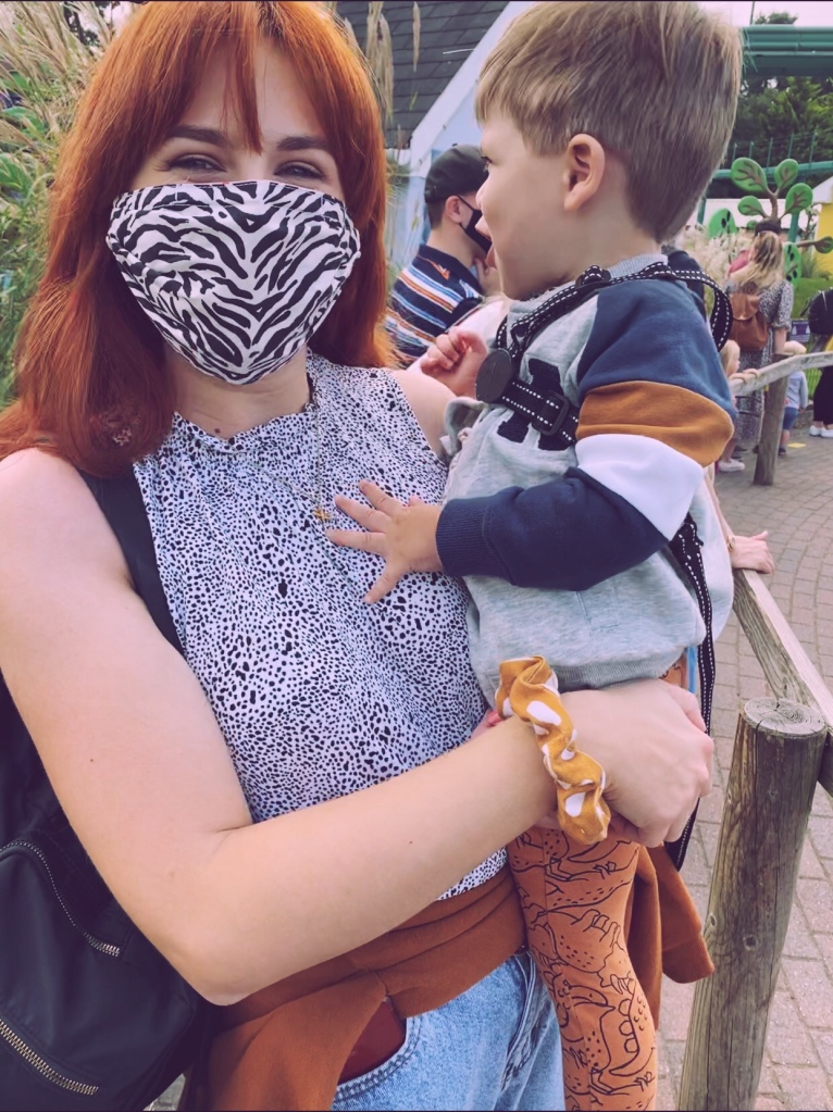 Mum wearing a zebra print face mask, smiling, whilst holding a little boy who is turned away from the camera. They are in a queue for a ride at Peppa Pig World