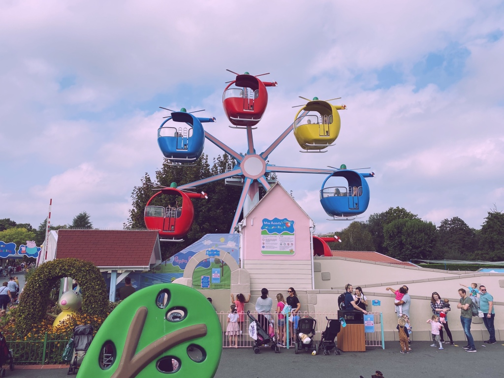 A childrens ride of helicopters in the style of a ferris wheel. there is a queue of people waiting to go on, who are all stood 1m plus from one another