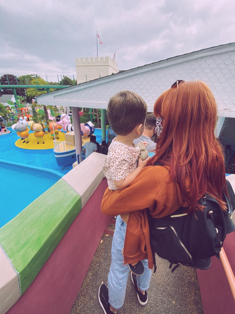 A mum with long red hair is holding a little boy, both backs are to the camera. They are queuing to ride a water ride with boats and many cartoon character figures