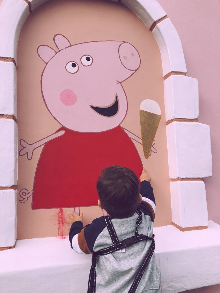 Little boy with his back to the camera, wearing a grey jacket pointing at a pink painting of Peppa Pig holding an ice cream